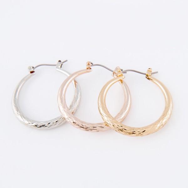 "Short hoop earrings featuring textured details.  - Approximately 1"" in diameter"
