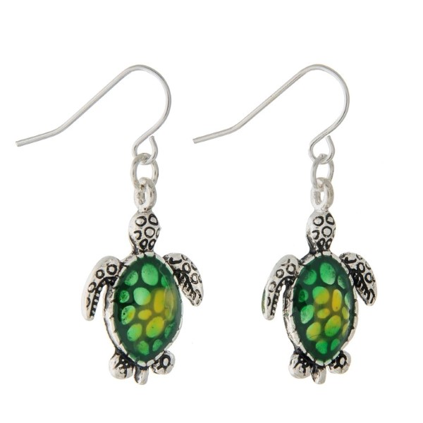 "1 1/4"" Silver tone fishhook style earrings featuring a small sea turtle shaped design accented by a green ombre style shell."