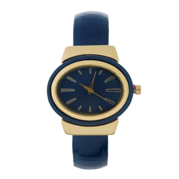 Cuff watch with a patent leather look, gold tone accents, and a monochromatic face.