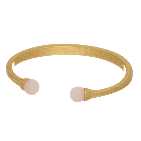 Matte gold tone cuff bracelet featuring two white beads at the opening.