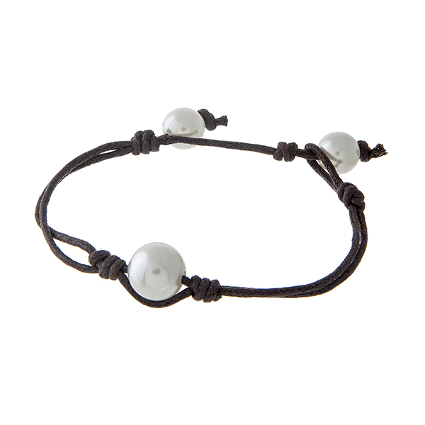 "Brown cord bracelet with a single faux ivory pearl focal. Approximately 8"" in length."