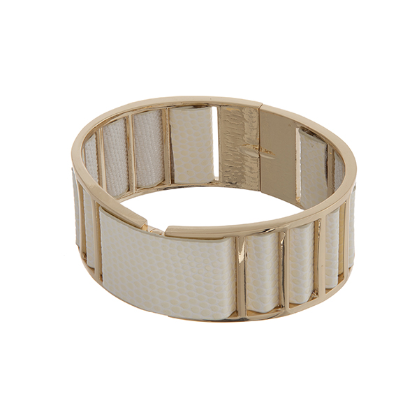 Gold tone cuff bracelet displaying ivory faux leather with a back spring lever.