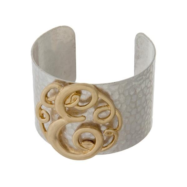 Hammered silver tone cuff bracelet with a gold tone script 'E' initial.