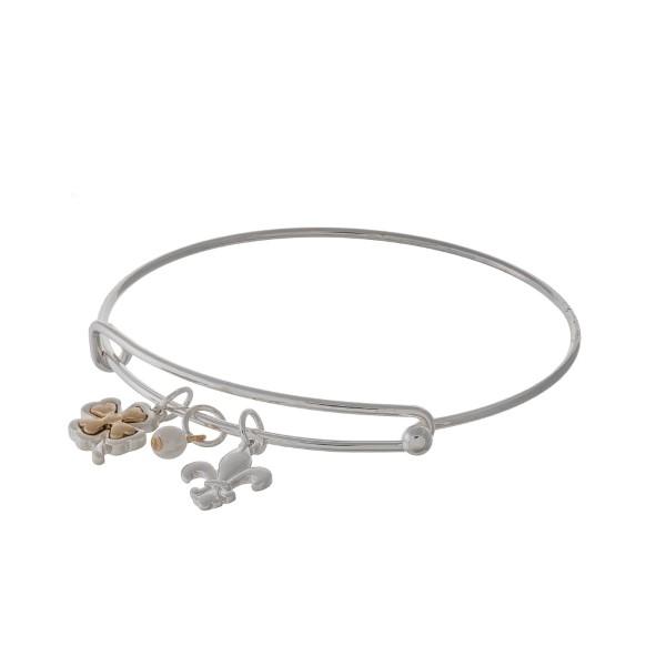 Silver tone adjustable bangle bracelet with a four leaf clover and Fleur de Lis charm.