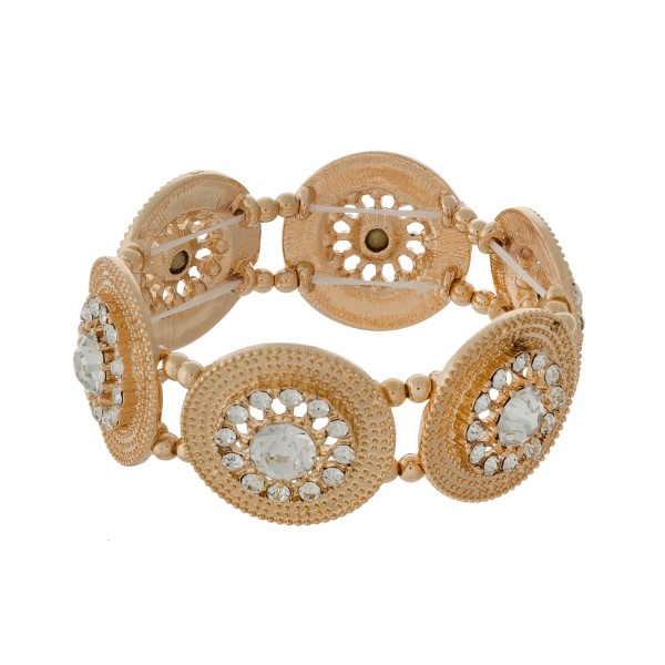 "Gold tone stretch bracelet displaying textured circles accented with clear rhinestones. Approximately 1.25"" in length."