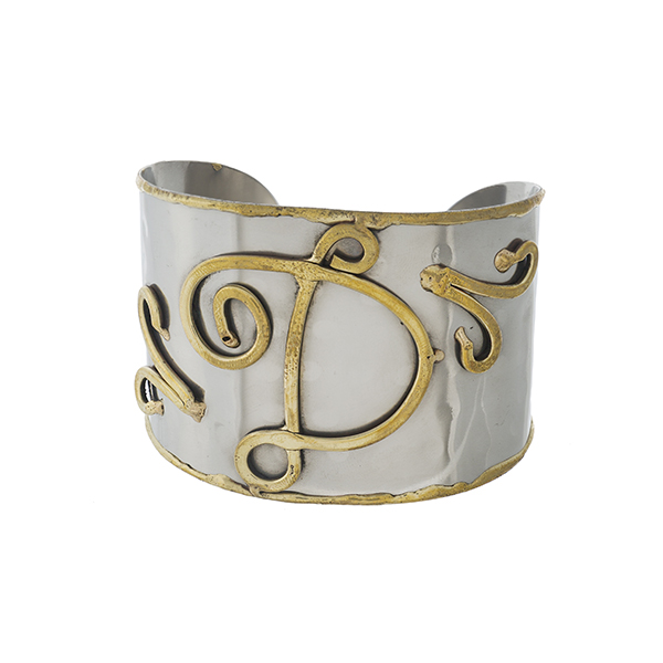 "Two tone, handmade, brass cuff bracelet with a script 'D' initial. Approximately 2"" in width."