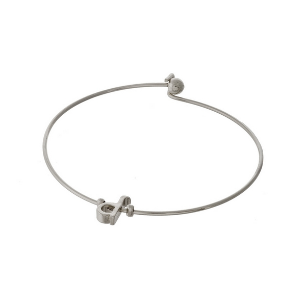 "Dainty silver tone bangle bracelet with a lowercase ""D"" initial."