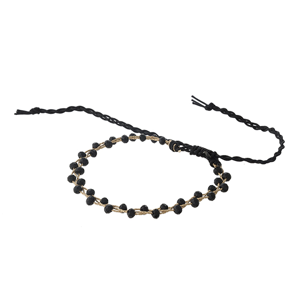 Black beaded bracelet with gold tone accents and a pull-tie closure.