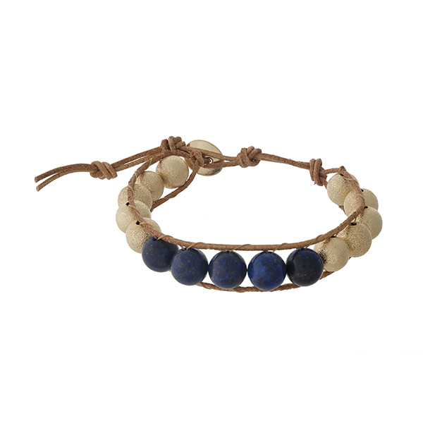 Brown cord bracelet with navy and gold tone beads and a button closure.