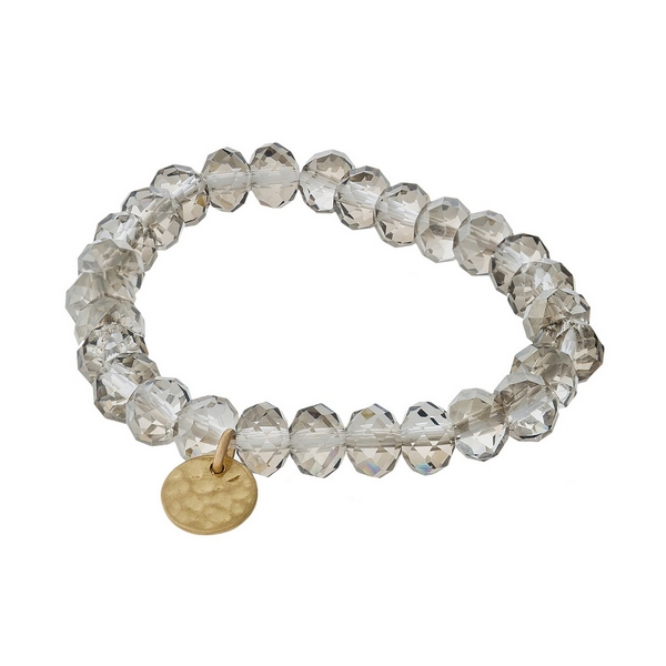 Smoke gray faceted bead stretch bracelet with a hammered gold tone circle charm.