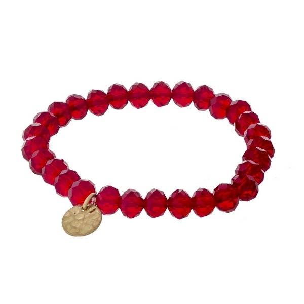 Crimson faceted bead stretch bracelet with a hammered gold tone circle charm.
