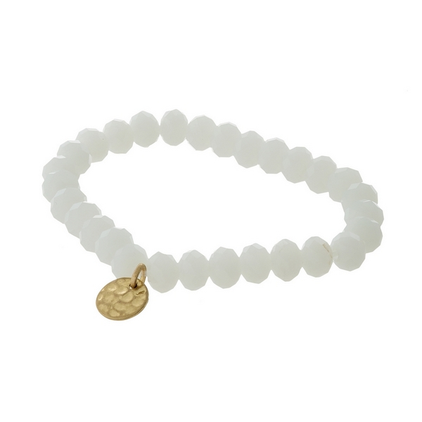 White faceted bead stretch bracelet with a hammered gold tone circle charm.