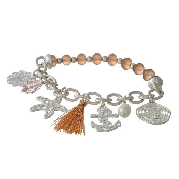Silver tone and peach beaded stretch bracelet displaying sealife and tassel charms.