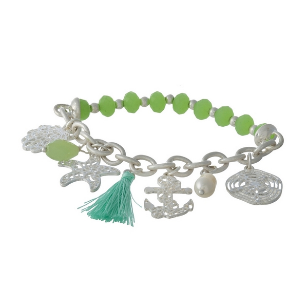 Silver tone and green beaded stretch bracelet displaying sealife and tassel charms.