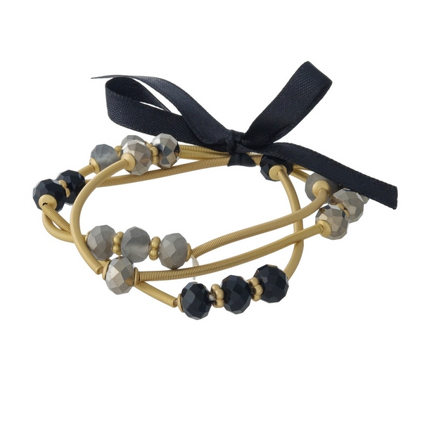 Three piece, gold tone, stretch bracelet set featuring black and gray faceted beads.