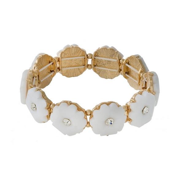 Gold tone stretch bracelet displaying white epoxy stone flowers with clear rhinestone centers.
