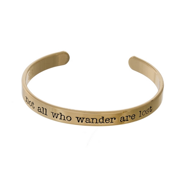 "Gold tone cuff bracelet stamped with ""not all who wander are lost."""