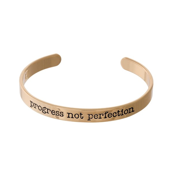 """Gold tone cuff bracelet stamped with """"Progress Not Perfection."""""""