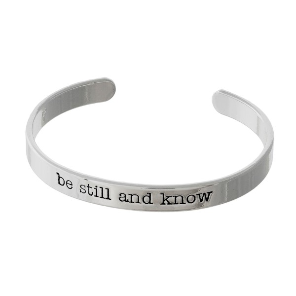 """Silver tone cuff bracelet stamped with """"be still and know."""""""
