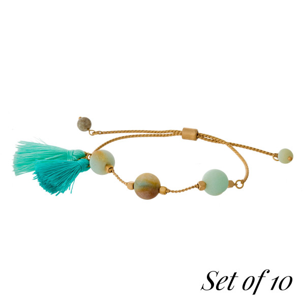 Set of 10, gold tone pull tie bracelets with natural stone beads and tassel accents. Set comes with the following natural stones: lapis, gray, picture jasper, beige, carnelian, labradorite, green, tiger's eye, dalmatian jasper, and amazonite.
