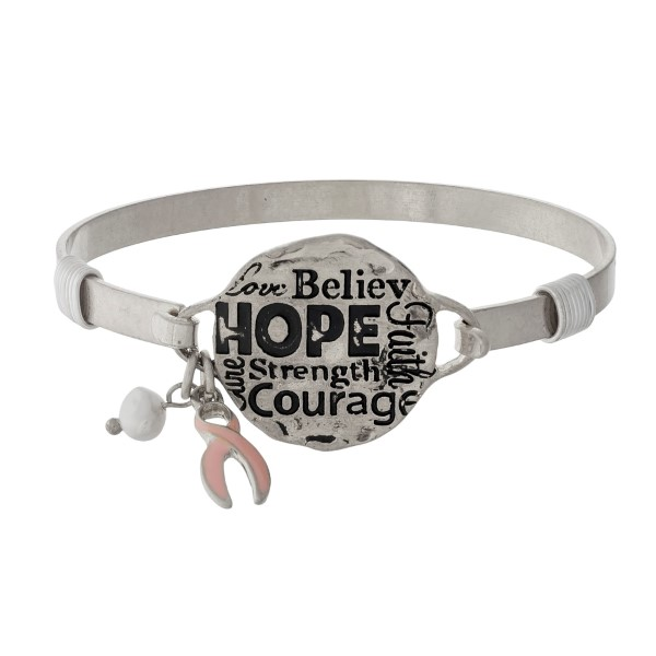 "Metal bangle bracelet with a circle focal stamped with ""Hope, Courage, Strength, Faith, Believe."""