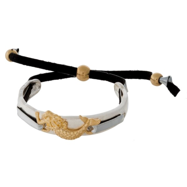 Hammered silver tone bangle bracelet with a gold tone sea life focal and a black cord closure.