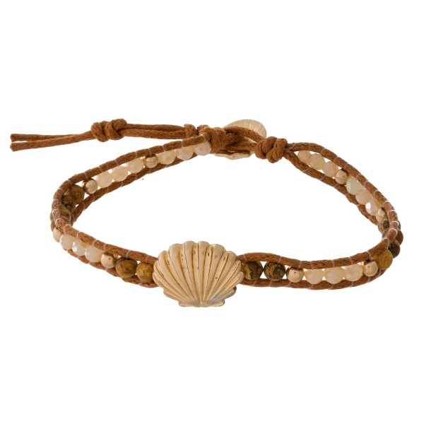 Ivory beaded and faux leather bracelet with sea life accents and a button closure.