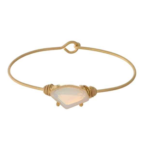 Dainty gold tone bangle bracelet with a rhinestone focal.
