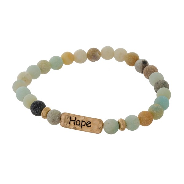 "Natural stone beaded stretch bracelet with a gold tone focal stamped with ""Hope."""