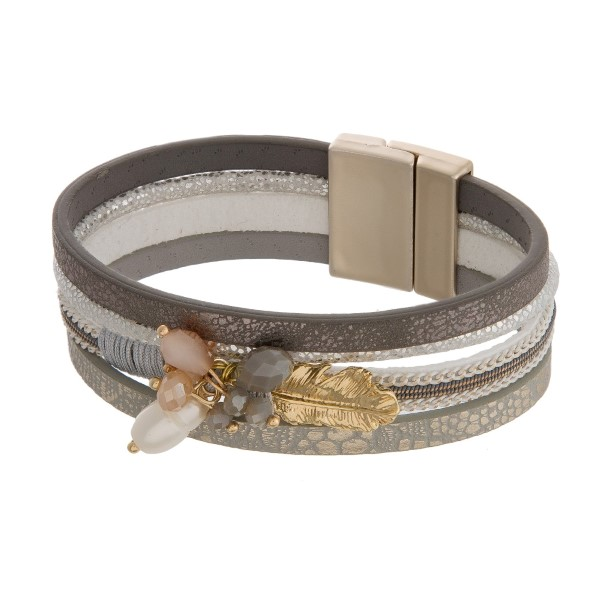 Faux leather bracelet with a metallic patter, bead charms and a feather charm.