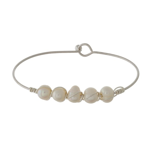 Dainty silver tone bangle bracelet with wire-wrapped, freshwater pearls.