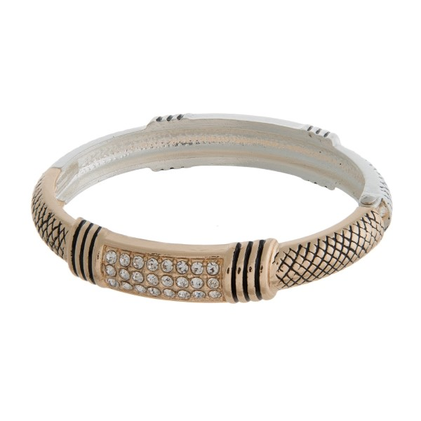 Silver and gold tone bangle bracelet with a hinge closure, and a tailored design.