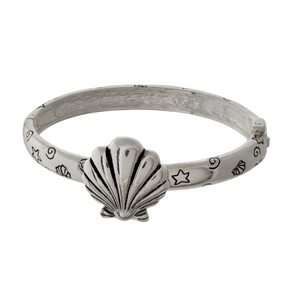 Silver tone bracelet with a seashell focal.