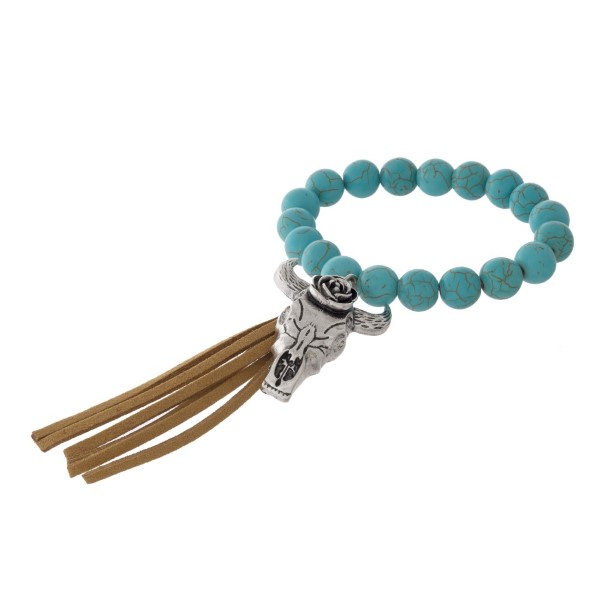 "Stretch bracelet with natural stone beads, metal charm, and 3"" leather tassel."