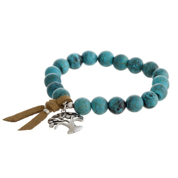 Beaded stretch bracelet with tree of life charm and faux leather tassel.