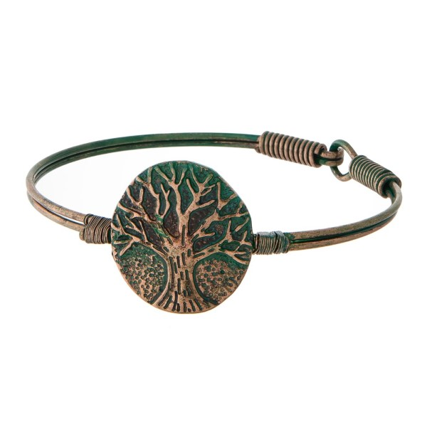Metal bracelet with latch closure and tree of life focal.