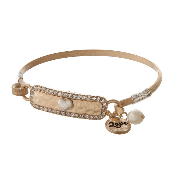 Metal bracelet with heart and pearl detail.