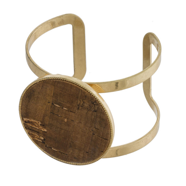 Gold tone cuff bracelet with cork circle focal.