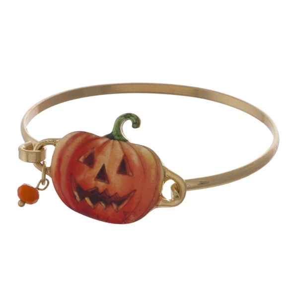 Gold tone metal bracelet with jack-o-lantern focal.