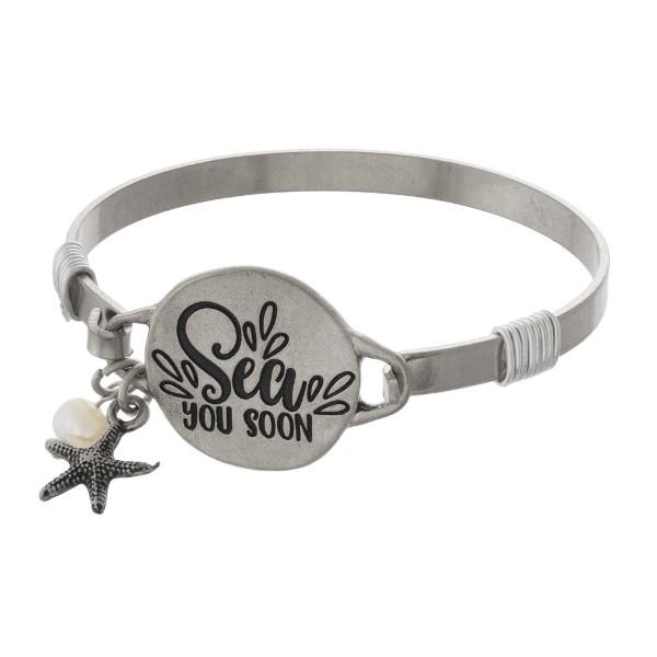 Metal bracelet stamped with Sea You Soon.