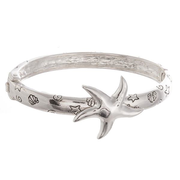 "Metal bracelet with sea detail and starfish wrist details. Approximate 3"" in diameter."