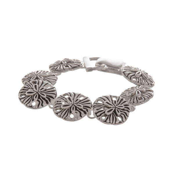 "Metal bracelet with flower  details. Approximate 7"" in length."