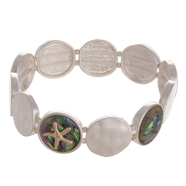"Metal stretch bracelet featuring mother of pearl and a gold starfish detail. Approximately 2.5"" in diameter unstretched. Fits up to a 5"" wrist."