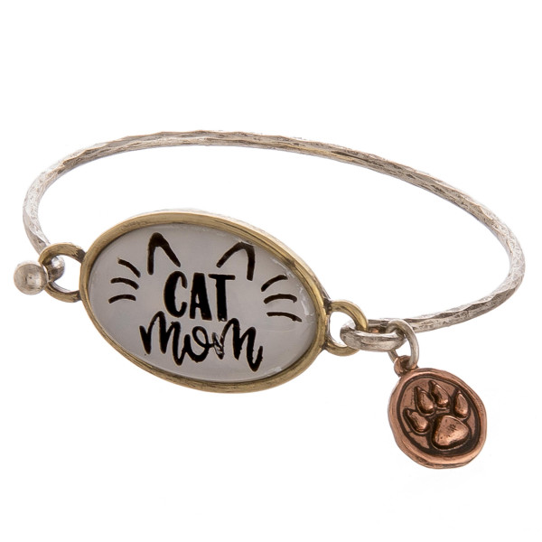 "Dainty bangle bracelet featuring a ""Cat Mom"" inspired focal with a paw print charm and hook closure. Approximately 2.5"" in diameter. Fits up to a 5"" wrist."