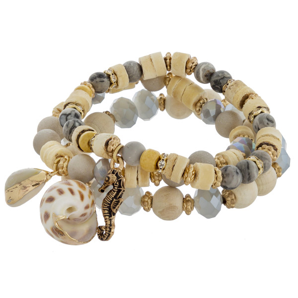 "Bracelet set featuring three beaded stretch bracelets with a seashell, puka shell, and seahorse charm and gold accents. Approximately 2.5"" in diameter unstretched. Fits up to a 5"" wrist."