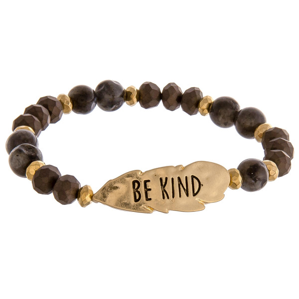 "Black beaded stretch bracelet featuring a gold feather shaped accent engraved with the phrase ""Be Kind."" Approximately 2.5"" in diameter unstretched. Fits up to a 6"" wrist."