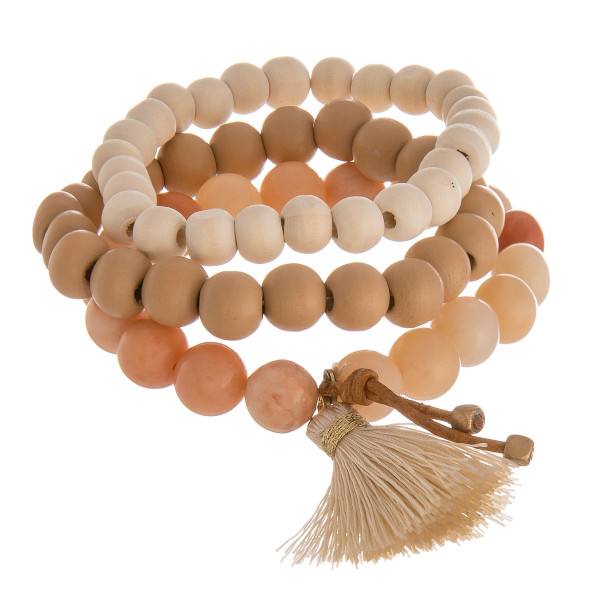 """Bracelet set featuring wood and natural stone beaded details with a tassel accent. Approximately 3"""" in diameter unstretched. Fits up to a 6"""" wrist."""