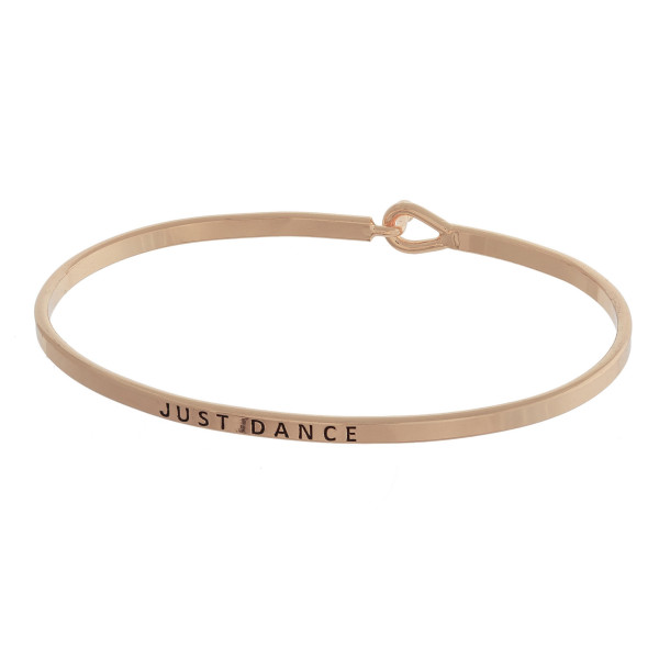 "Dainty metal bracelet featuring ""Just Dance"" engraved message with a hook closure. Approximately 2.5"" in diameter. Fits up to a 5"" wrist."
