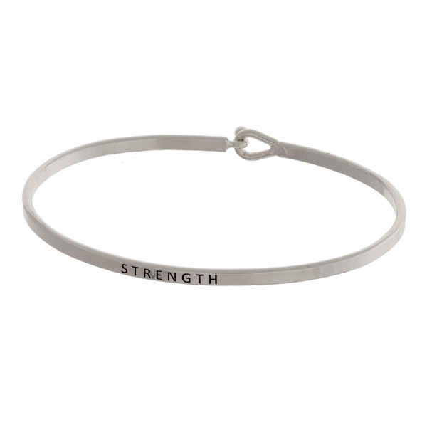 """Metal bracelet with engraved message """"Strength."""" Approximate 2"""" in diameter."""