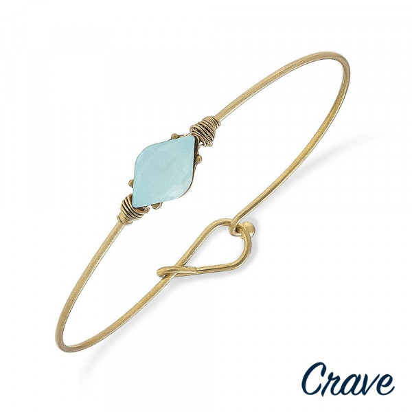 "Dainty gold metal bracelet with a crystal inspired focal. Approximately 2.5"" in diameter."